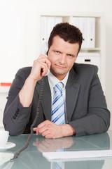 geschäftsmann führt ernsthaftes telefongespräch