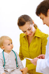 Pediatric doctor explaining something to mother with baby