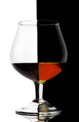 Glass of cognac on white-black background