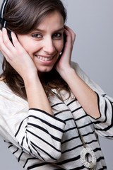 Smiling young woman listening to music over gray background