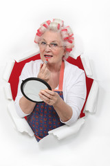 Old woman in rollers putting on lipstick