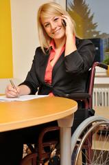 Frau im Rollstuhl telefoniert