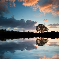 Stunning sunset silhouette reflected in calm lake water