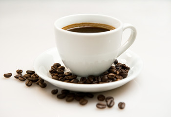 Cup of coffee and beans over white background
