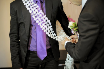 Pinning a decorated lace ribbon at wedding party