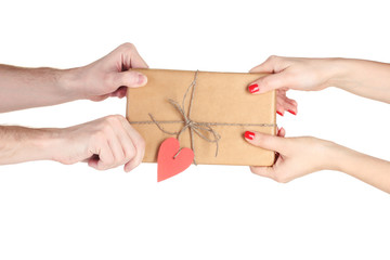 Man's hand giving parcel with blank heart-shaped label to woman