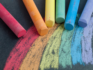 Rainbow colored pieces of chalk with a drawing on a blackboard