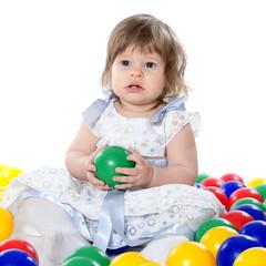 The little girl plays multi-coloured balls