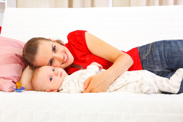Smiling mother with baby laying on couch
