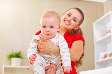Smiling mother and adorable baby playing at home