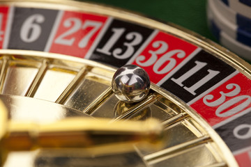 Gold roulette and gambling chips on a green background