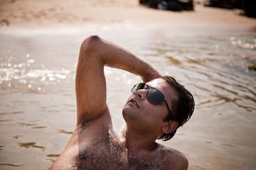 Indian man swimming at ocean beach