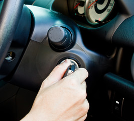 a hand turning the key to start the car