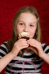 young girl eating a delicious cupcake