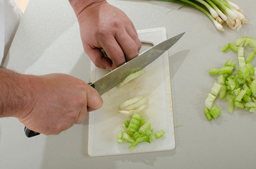 latin american man chopping onion leaves and celery