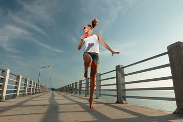 Girl run and jump in sunset on a pier with watermelon heart