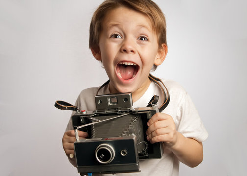 Happy photographer boy ,child ,kid taking a picture with a Polaroid style instant camera