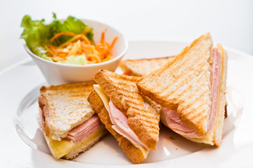 Toast with ham and cheese on the white plate with the bowl of gr
