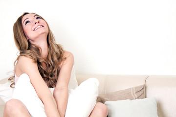Lachende junge Frau auf der Couch mit Kissen