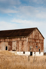 An old weathered bank barn with fields in the foreground