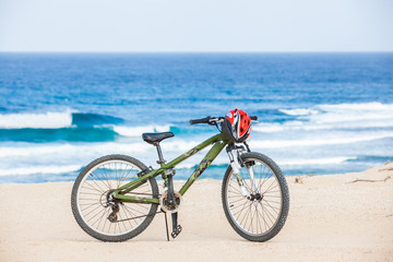 Autocollant pour porte Velo Bicycle with helmet, stand on the beach.