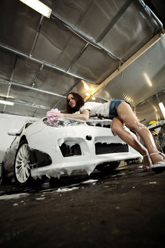 beautiful girl washes the car