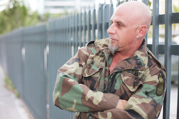 Military man leaning on the fence