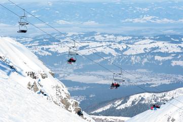 Narciarze na kolejce krzesełkowej i panorama z gór