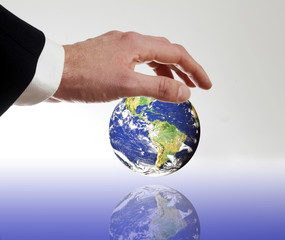 Mann mit Anzug legt beschuetzend seine Hand ueber die Erde