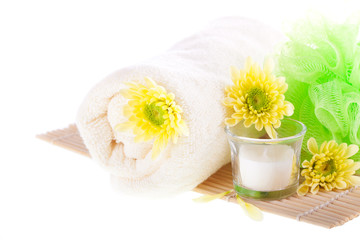 Towel, flowers, candle and bamboo mat on white. Spa concept