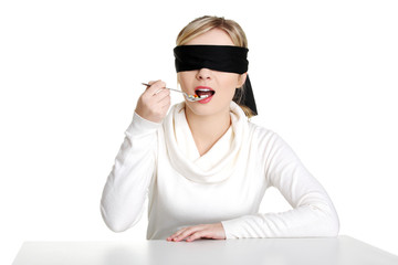 Blindfold woman holding spoon with pile of pills