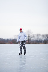 Handsome young man ice skating outdoors on a pond on a cloudy wi