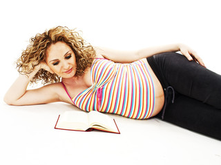 The pregnant woman reads the book. Isolated on white