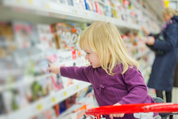 Little girl at magazines section in supermarket