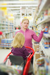Mother and daughter in baby food section in supermarket