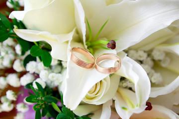 Gold wedding rings on flower