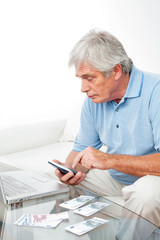 Senior am Laptop mit Taschenrechner