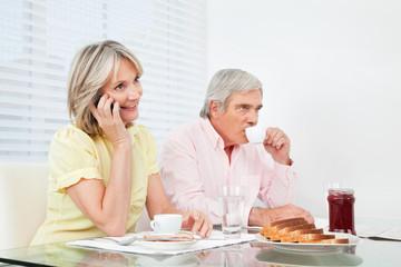 Seniorin telefoniert beim Frühstück
