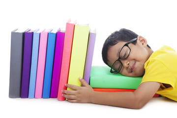 Fotobehang - Smart toddler with glasses sleeping with books