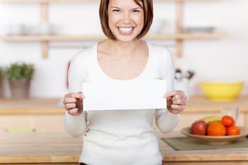 lachende frau in der küche zeigt schild