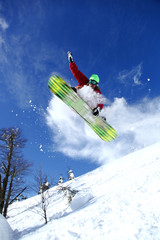 Wall Mural - Snowboarder jumping against blue sky
