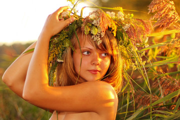 Portrait at sunset: beautiful young girl on grass