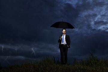Businessman standing in thunderstorm