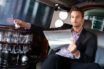 Handsome man reading newspaper in limousine