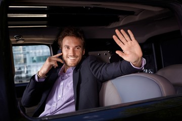 Celebrity waving from limousine window smiling