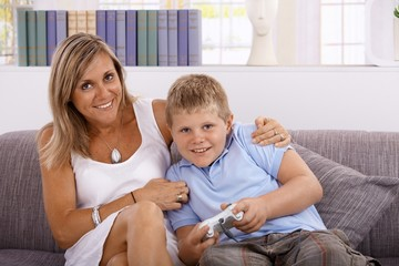 Little boy and mother playing video game smiling