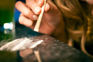 Young woman snorting cocaine