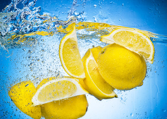 Deurstickers Opspattend water Lemon Slices falling deeply under water with a big splash on blu