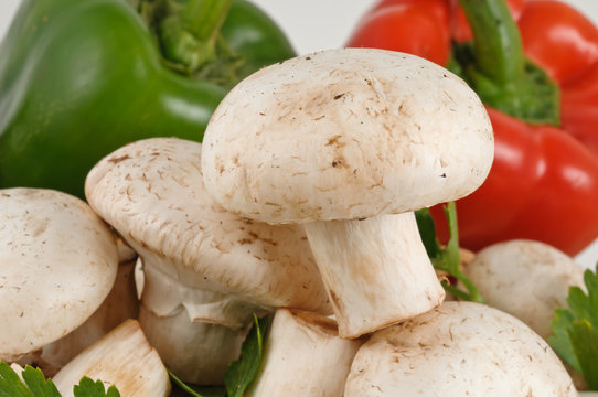 Tasty fresh white mushrooms with peppers on background