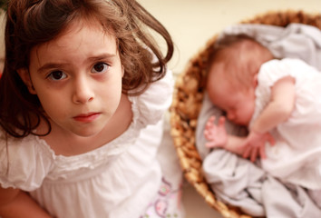 5-year-old girl is holding her newborn sister